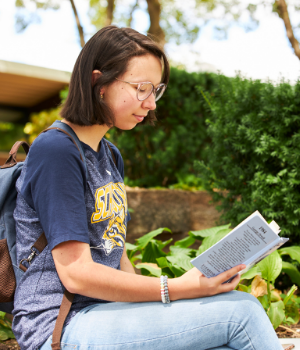 Student sits outside reading a book