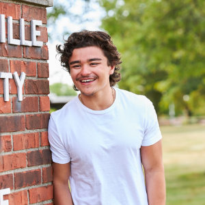 Student smiling leaned up against a brick wall