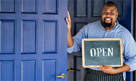 """Man holding an """"open"""" sign outside of a business"""