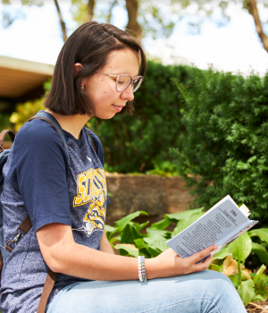 Student reading a book outside